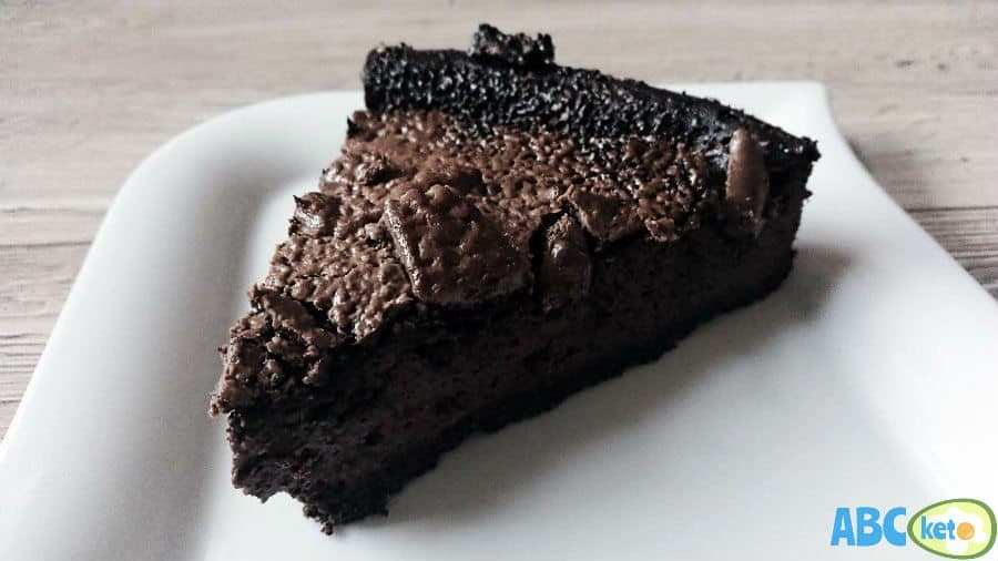 Keto chocolate cheesecake with chocolate topping, piece of keto chocolate cheesecake